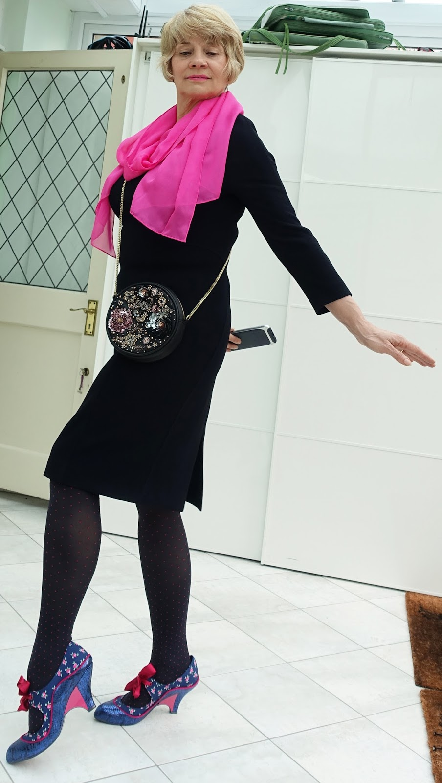 How to use accessories to transform a dull outfit, in this case a plain navy shift dress, Over 40s blog Is This Mutton? adds fuchsia pink and blue and a cute sequinned bag.
