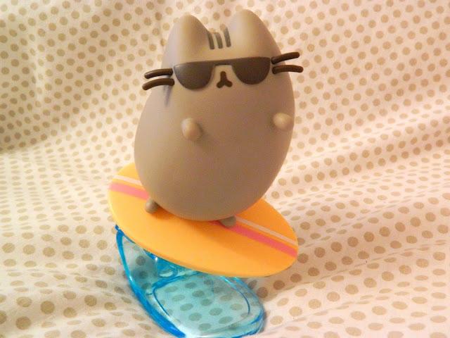 A summer-themed vinyl figure of Pusheen as a surfer riding a wave