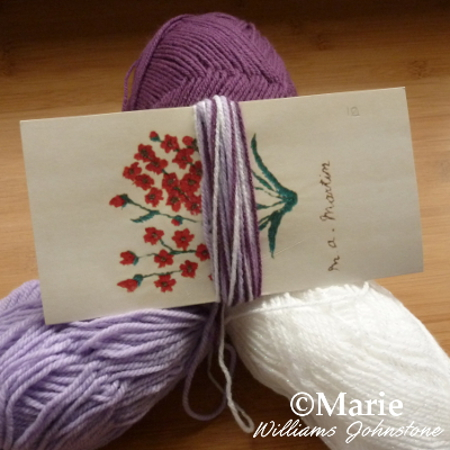 Wrapping yarns around a piece of card to make a tassel from acrylic wool yarns