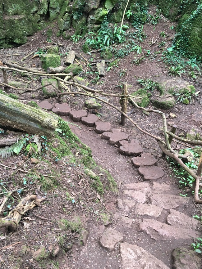 looking down hill logs stepping stones cut to look like dinosaur footprints