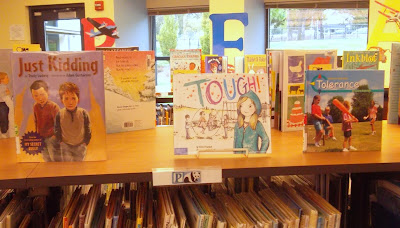 Books stood upright on shelf-top, their covers facing outward. From left to right, the books are 'Just Kidding' by Trudy Ludwig, 'Tough!' by Erin Frankel and 'Tolerance' by Lucia Raatma