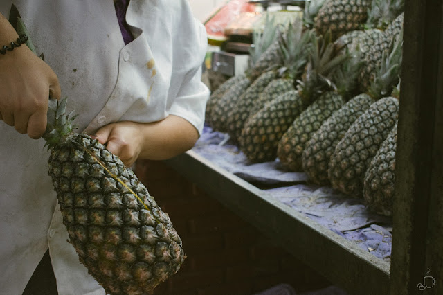 mulher descascando abacaxi na praça do abacaxi dentro do mercado central de belo horizonte