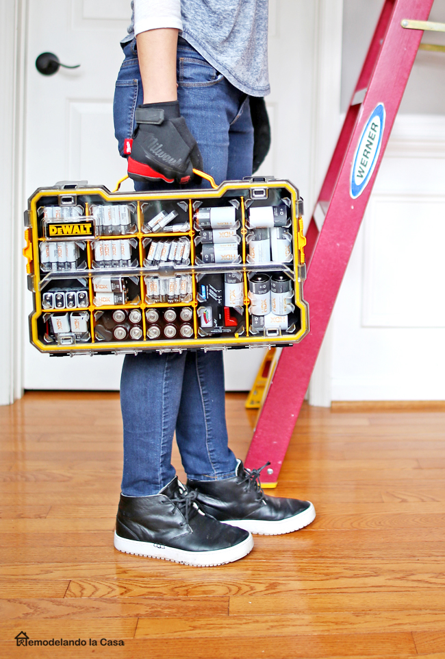 Cristina Garay holding yellow dewalt 20 compartment pro small part organizer packed with HDX alkaline batteries