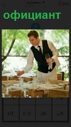 официант в ресторане расставляет приборы на стол