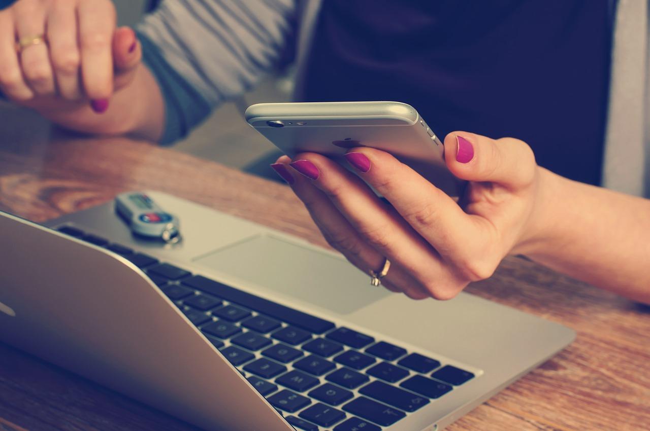 #PraCegoVer Na imagem temos as mãos de uma mulher, segurando o celular. Na sua frente há um computador e um pendrive.