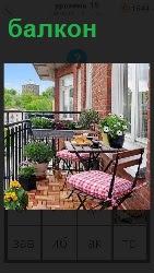 На свежем воздухе открытый балкон, на котором стул и столик с вазой и цветами внутри