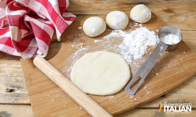 balls of bread dough on counter; one flattened with rolling pin