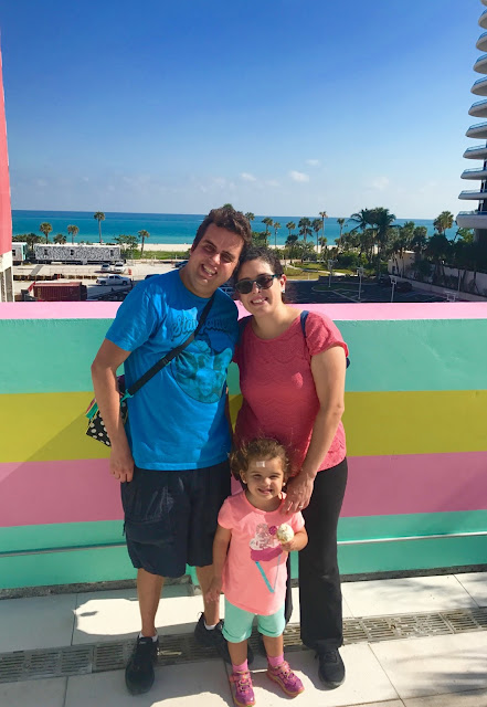 A family of three pose for a photo on a colorful balcony with the beach in the background