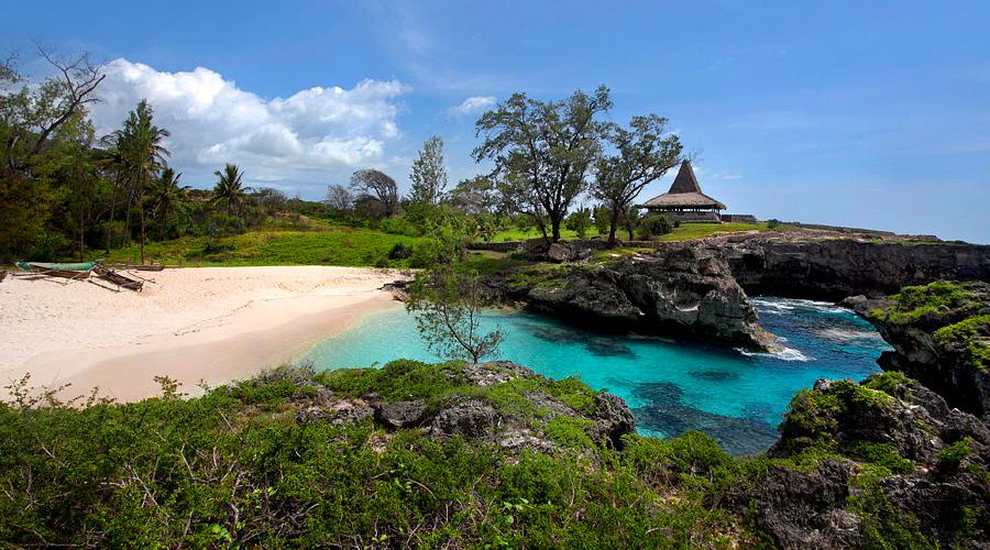karang di pantai Pantai Mandorak kuil dan bangunan desa