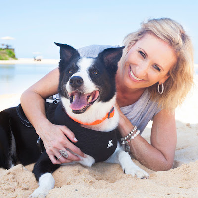 Anneke van den Broek CEO of Rufus & Coco and her dog lying on a beach