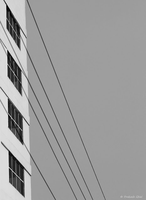 A Black and White Looking Up Minimal Art Photo of Four Windows of a Building and Electricity Wires Overlapping them.