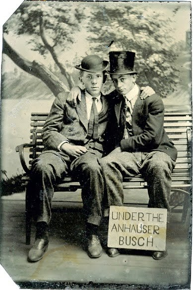 Photo c. 1900s, two young men posing on a park bench with arms around their shoulders, pose with a sign. Under the Anhauser Busch.  Jingles and other stories of The American Dream. marchmaton.com