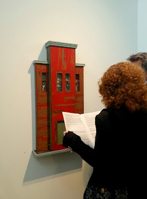 Two people looking at an exhibition catalogue in front of an Alex Asch piece hanging on the wall.