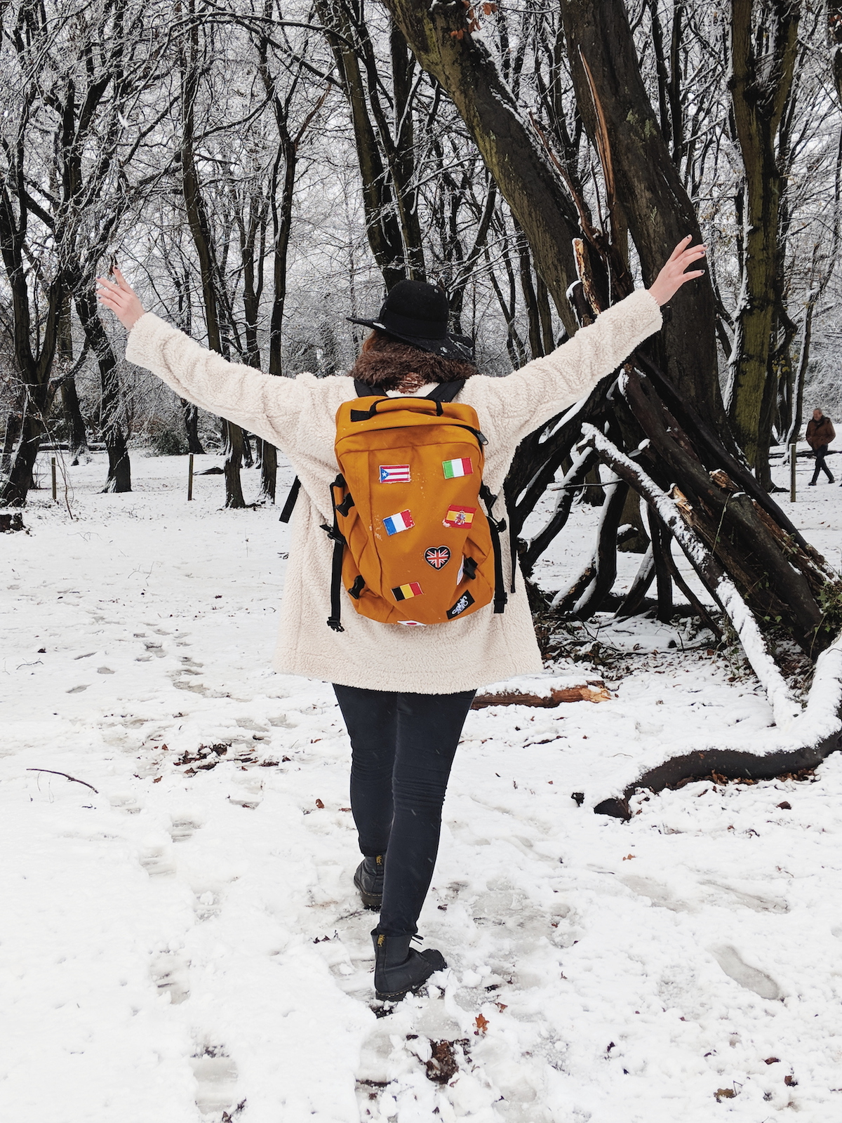 Travel blogger, Leigh Travers, walks amongst a snowy forest scene with her hands in the air whilst wearing a Cabin Zero rucksack