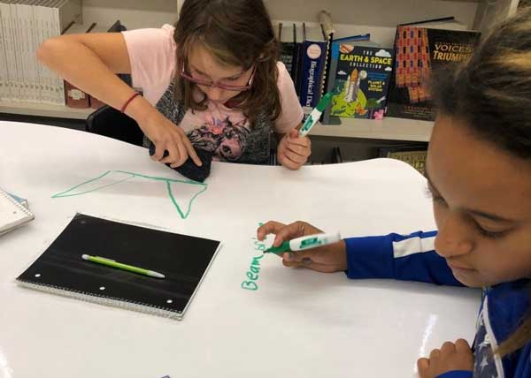 girl and boy using whiteboard tables to brainstorm and plan their STEM based projects