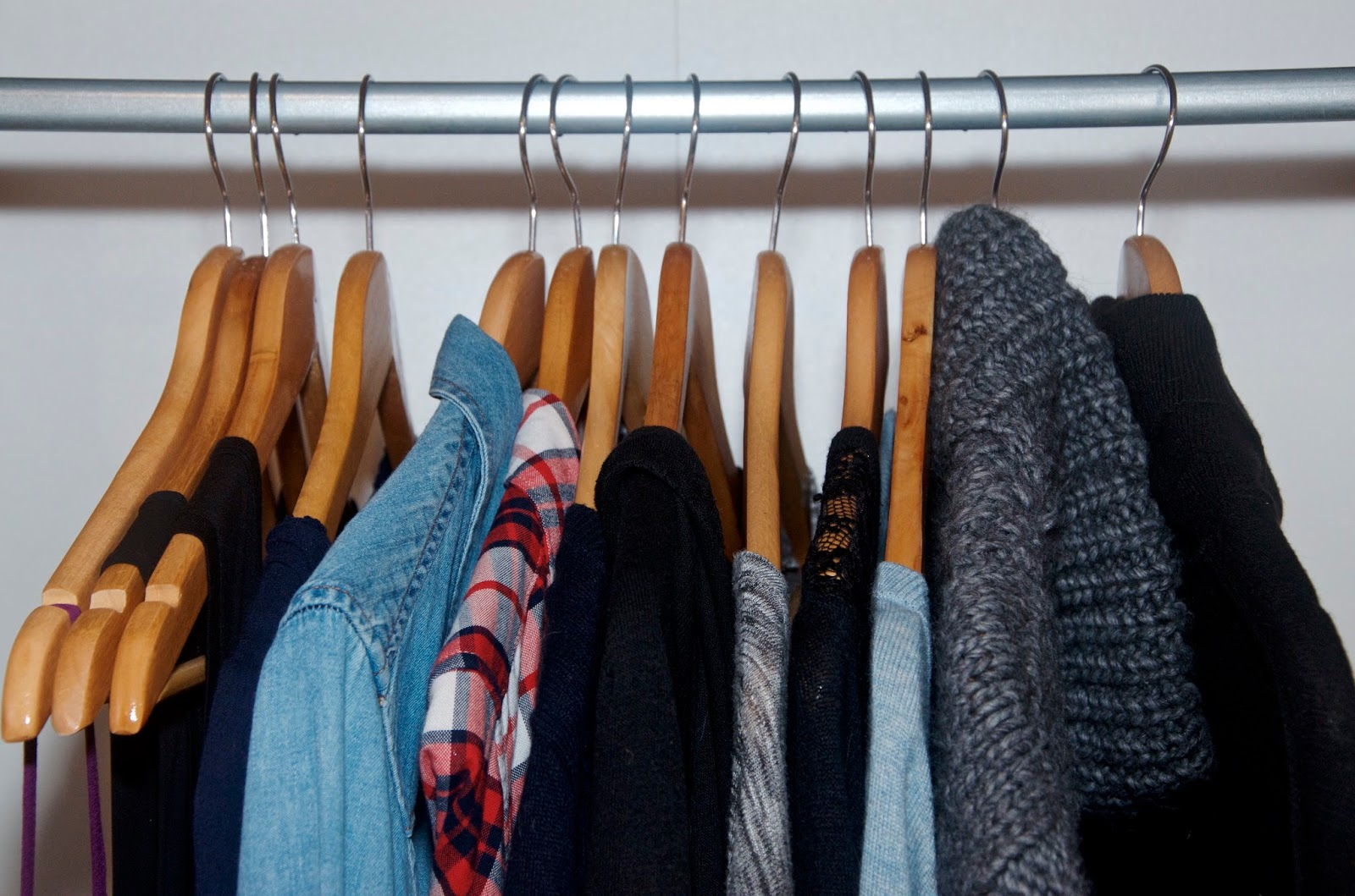 Closet with clothes on wooden hangers