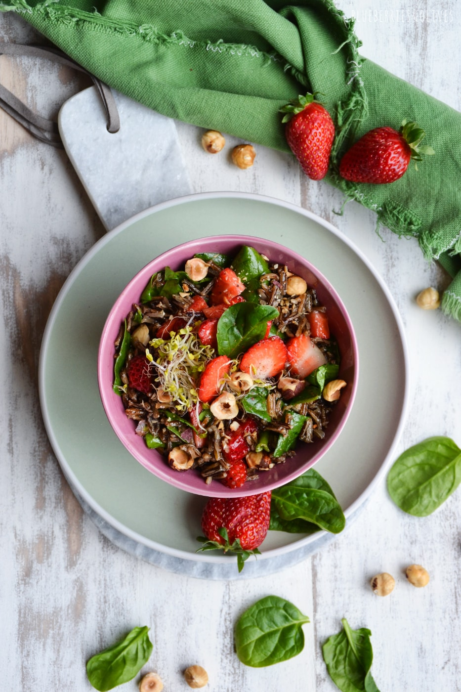 WILD RICE SALAD WITH STRAWBERRIES IN A PINK BOWL, GREEN DISH AND CLOTH, WHITE BACKGROUND