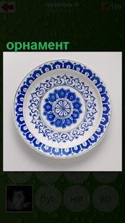 стоит тарелка, на которой нанесен орнамент синего цвета
