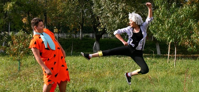 Woman Bouncing Around and Man Dressed as Fred Flintstone Dodging Her Kick