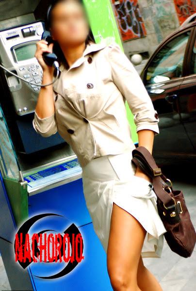 escort luciendo pierna junto a cabina telefonica
