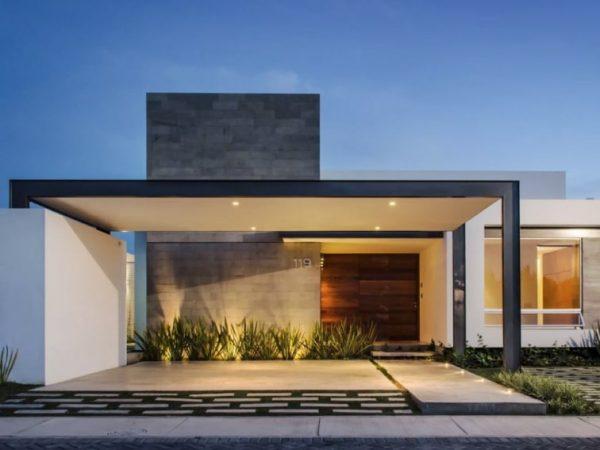 Casa con diseño moderno con vegetación en acceso.