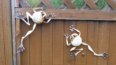 Decorative metal frog sculptures on the fence.
