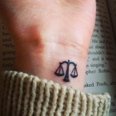 vemos la muñeca del brazo de una mujer con un tatuaje de libra