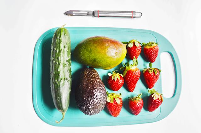 pelador plateado acompañado de una tabla verde cortas donde esperan las frutas