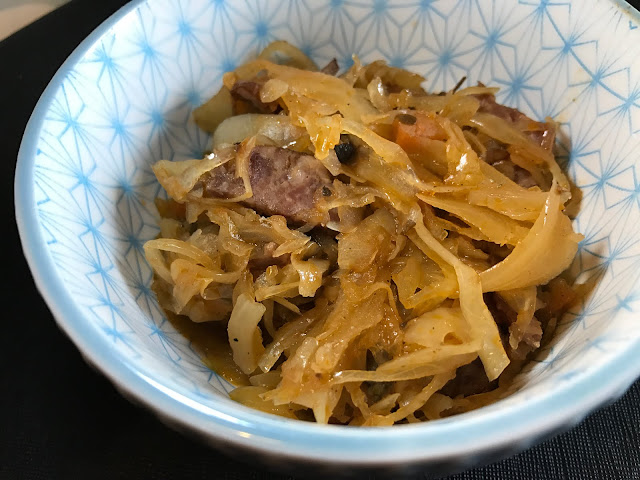 A small white bowl with a blue pattern with shredded cabbage, sausage and other ingredients which make up bigos