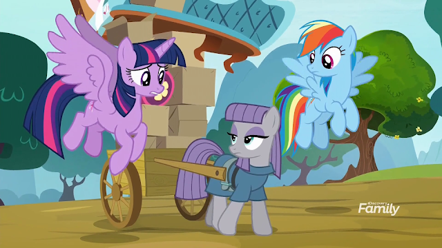 Maud Pie pulling a cart of her sister's possessions as Twilight and Rainbow fly alongside.