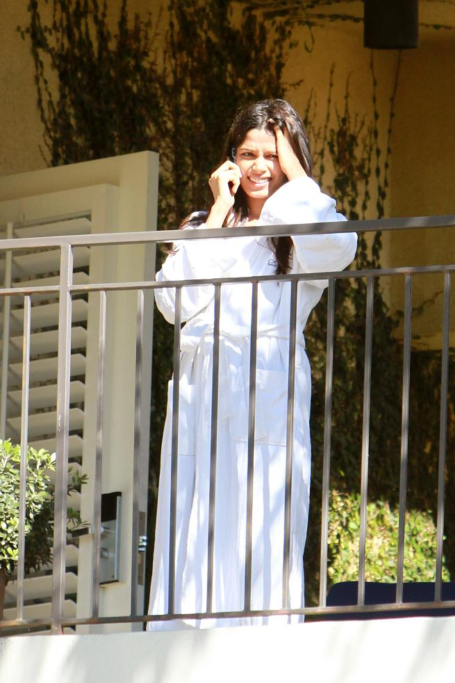 Freida Pinto in a bathing robe on hotel balcony