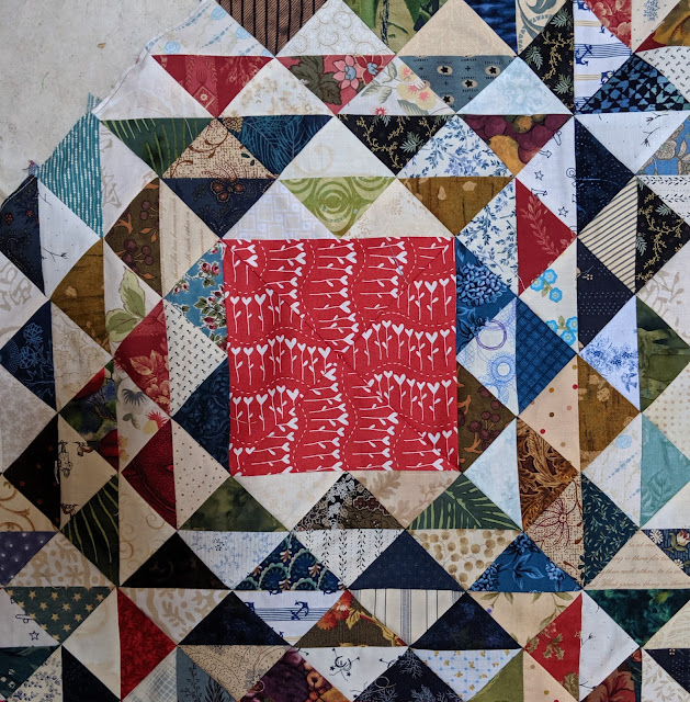 One scrap quilt block with a large red and white print square in the center.
