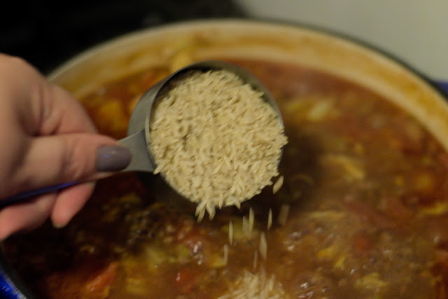 Uncooked rice being added to the pot.
