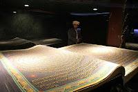 Yüce Allah'ın büyük sözlerinden devasa bir Kuran Kitabını okuyan bir Müslüman