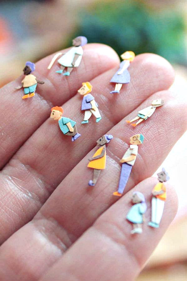 miniature, colorful paper cut figures shown on a hand for scale