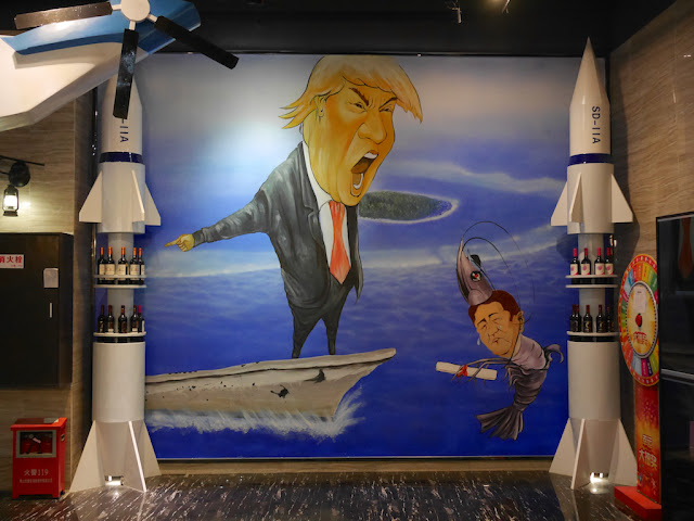 mural of Donald Trump pointing from a ship and Shinzo Abe made to look like a shrimp
