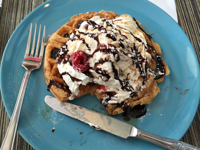 A waffle covered in cream, berries and chocolate sauce