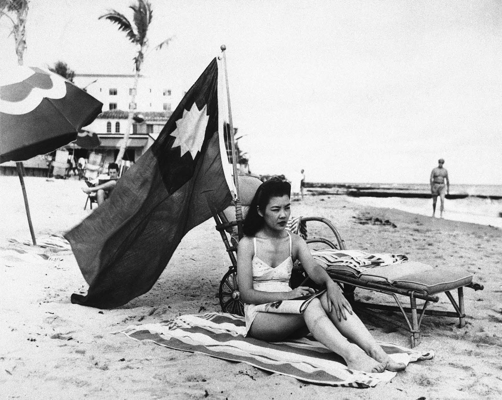 Ruth Lee, a hostess at a Chinese restaurant, flies a Chinese flag so she isn't mistaken for Japanese when she sunbathes on her days off in Miami, in the wake of the attack on Pearl Harbor, Dec. 15, 1941. The flag shown here is the flag of Nationalist China which went into self imposed exile to the island of Taiwan after the Communist revolution. This flag is now the flag of Taiwan.