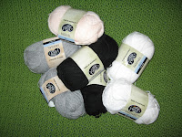 Seven skeins of acrylic yarn in light grey (2 skeins), flesh (1), black (2) and white(2).