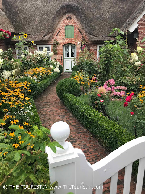 Path through a cottage garden leading to the white and green wooden door of a red brick cottage..
