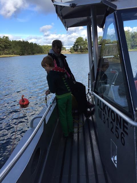 Poika laskee kameraa veneestä veteen.