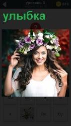 Девушка с улыбкой и венком на голове расправляет свои длинные прекрасные волосы