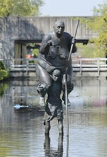 Survival of the Fattest is a sculpture of a small starving African man, carrying Lady Justice, a huge obese European woman who is a symbol of the rich world.