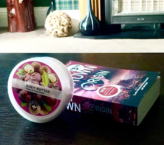 A stood up wide cylindrical tub with a pink label with Superdrug Cherry and Macadamia Nut Body Butter in black font with a picture of red cherries next to it  next to a rectangular book saying dan brown in white font on a brown rectangular table  on a bright background