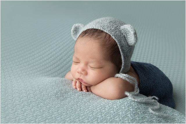 Newborn baby boy sleeping with his head on hands.