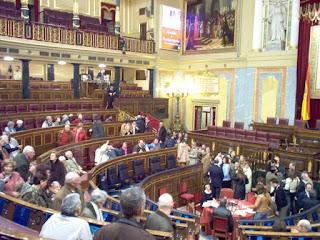 Vista parcial del interior del Congreso de los Diputados con visitantes sentados en los escaños en un día de puertas abiertas