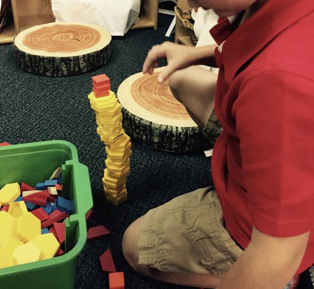 kindergarten child during math workshop stacking blocks