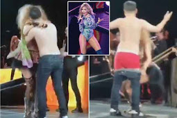 Pop star stuns fans by pulling a man on stage during concert before stripping his clothes