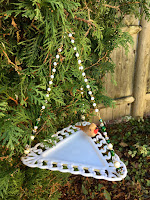 This hanging dish bird feeder features a triangle shaped white glass plate with scalloped edges.