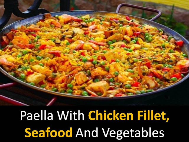 Paella with chicken fillet, seafood and vegetables